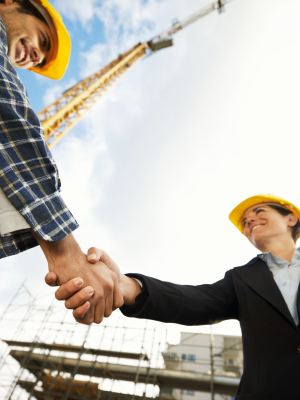 Construction workers shaking hands making a deal.