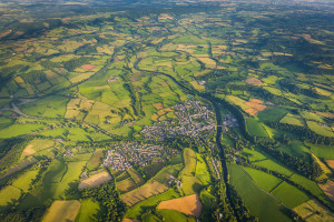 Country town surrounded by green fields pasture farmland aerial view