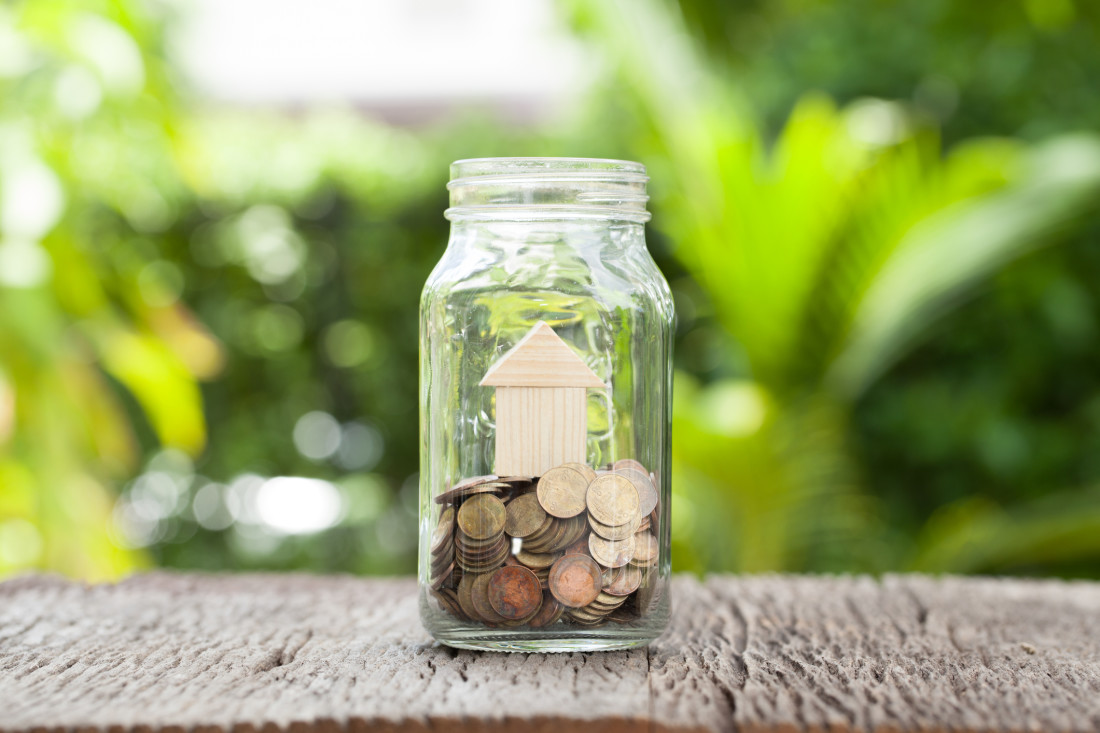 Money and house in glass jar